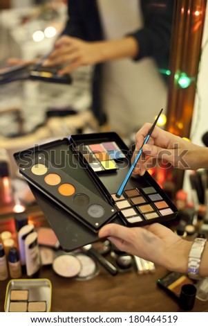 hands holding makeup colorful palette and eyeliner - stock photo