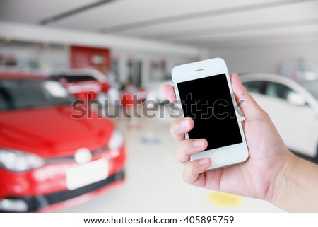 hands holding mobile phone with new cars in showroom dealership - stock photo