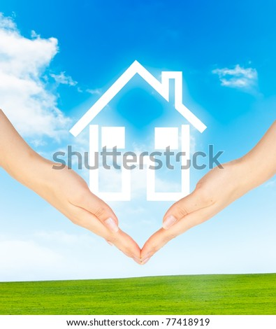 Hands holding model of a house on nature background - stock photo