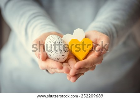 Hands holding modern painted easter egg and paper hearts. Toned picture