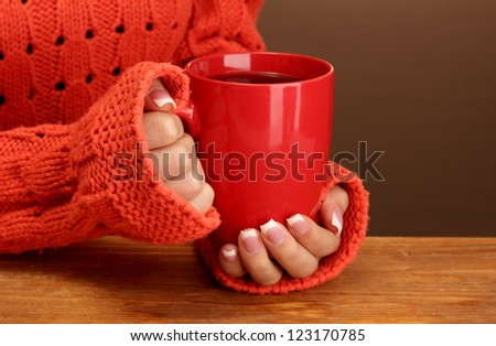 hands holding mug of hot drink, close-up - stock photo