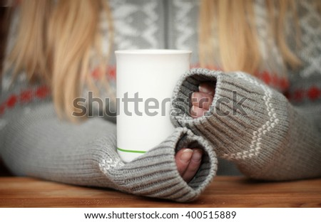 Hands holding mug of hot drink. Shallow depth of field. - stock photo