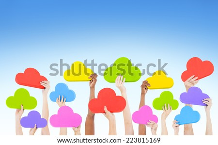 Hands holding multi colored cloud shaped speech bubbles with blue sky. - stock photo