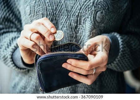Hands holding one euro coin and small money pouch - stock photo