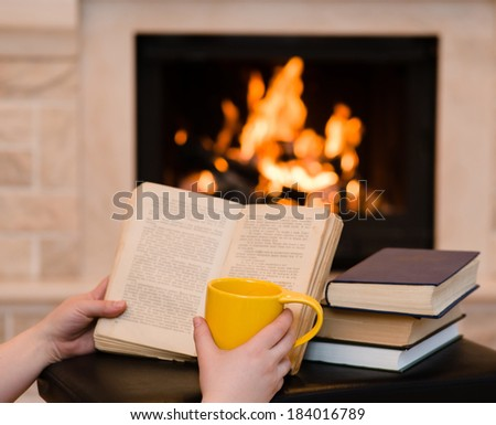 hands holding open book and cup of coffee near the fireplace - stock photo
