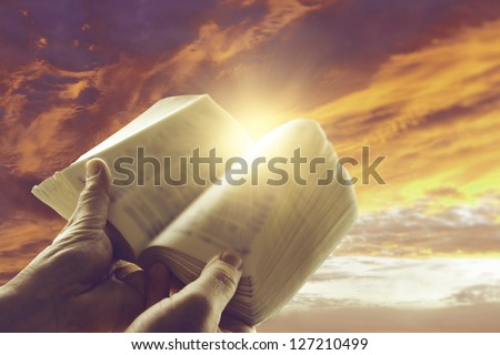Hands holding open book in front of sky - stock photo