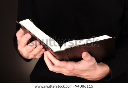 Hands holding open russian bible on black background - stock photo