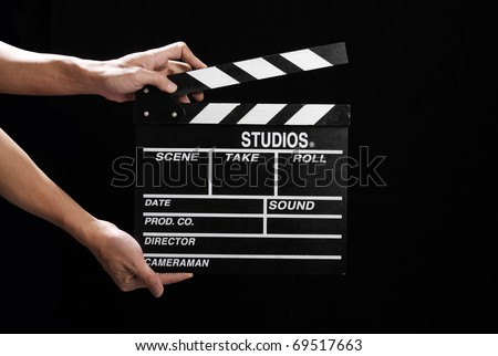 Hands holding out a clapper in black - stock photo