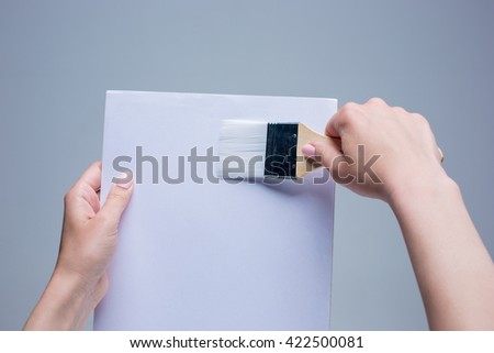 Hands holding painting brush on white canvas - stock photo