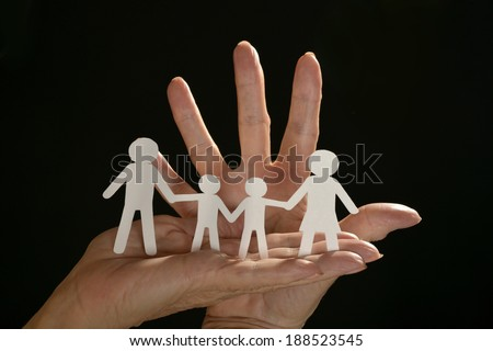 Hands holding paper family on black background - stock photo