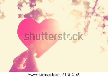 Hands holding paper heart. Instagram effect - stock photo
