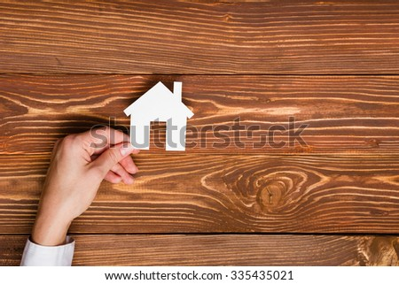 Hands holding paper house figure on wooden background. Real Estate green house Concept. Ecological building. Top view. - stock photo