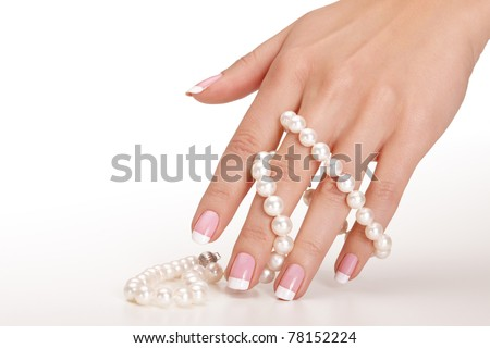 Hands holding pearls over seamless background - stock photo