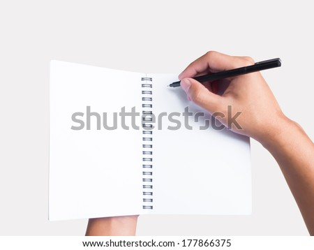 Hands holding pen and notebook isolated on grey background - stock photo
