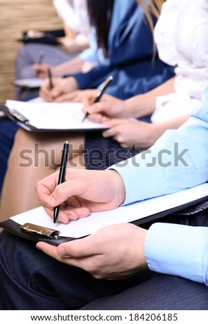 Hands holding pens and making notes at conference