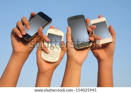 hands holding phones with blue sky as background - stock photo