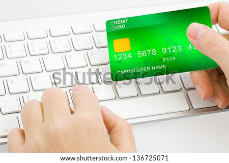 hands holding plastic card  and typing on open notebook background - stock photo