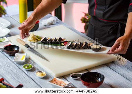 Hands holding plate with sushi. Sushi rolls with spices. Futomaki rolls cooked by chef. Tastiest dish in japanese restaurant.