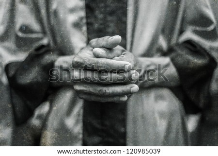 Hands holding praying of a male adult wearing baptizing cloths - stock photo