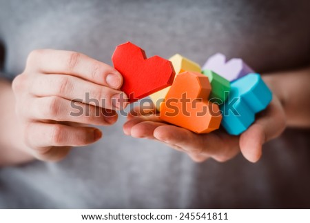 Hands holding  rainbow paper hearts, LGBT symbol. Toned picture - stock photo
