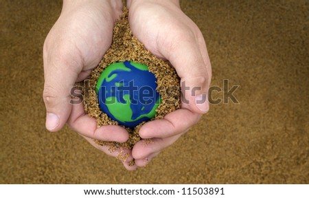 hands holding sand with small green and blue earth - stock photo