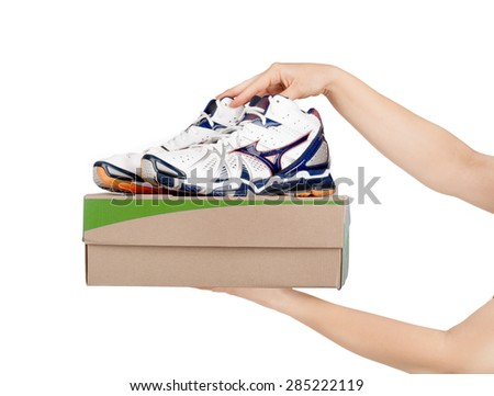 hands holding shoes in a box isolaterd on white  - stock photo