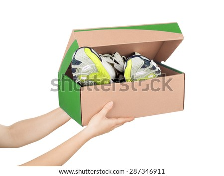 hands holding shoes in a box isolaterd on white background - stock photo