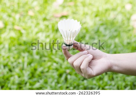 hands holding shuttlecock on the grass background