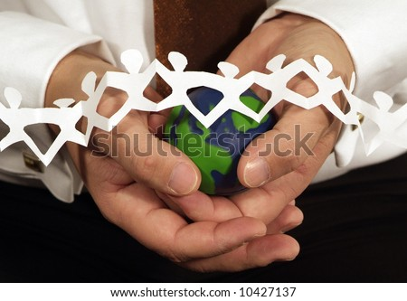 hands holding small green and blue globe with mini paper people across the globe - stock photo