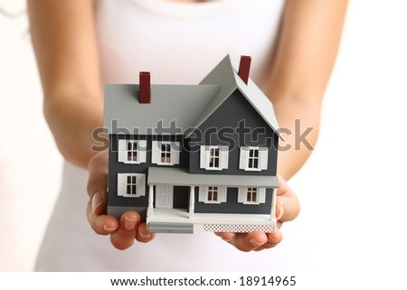 Hands holding small house - stock photo