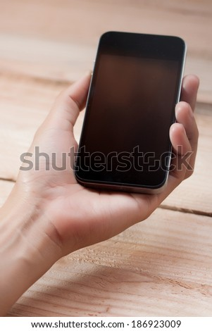 Hands holding smart phone on wood background