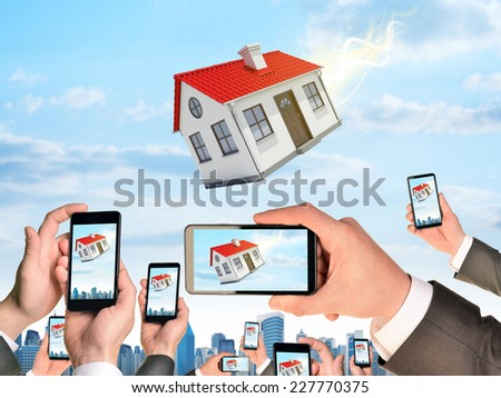 Hands holding smart phones and shoot video as falling house. City on background - stock photo