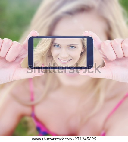 Hands holding smartphone against portrait of attractive young woman sitting on a lawn - stock photo