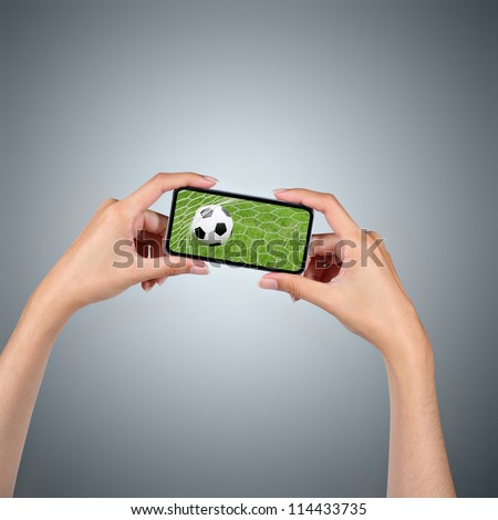Hands holding smartphone with soccer ball background - stock photo