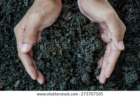 Hands holding soil - stock photo