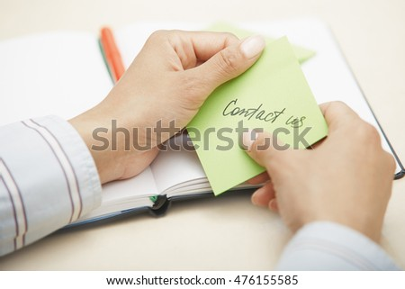Hands holding sticky note with Contact us text
