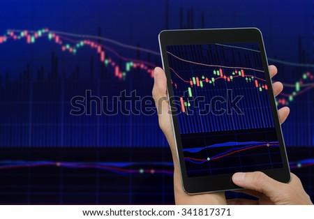 hands holding stock exchange  screen tablet computer with blurred stock exchange screen  background. - stock photo