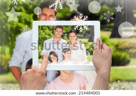 Hands holding tablet pc against white scales in front of storm clouds