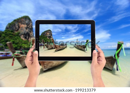 Hands holding tablet taking pictures at Railay beach in Krabi, Thailand