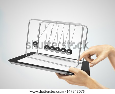 hands holding tablet with newton's cradle on a gray background - stock photo