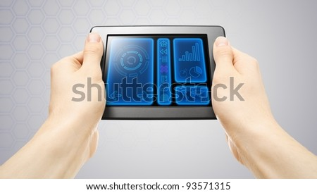 Hands holding tablet with screen showing futuristic interface. - stock photo