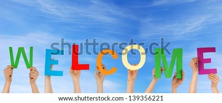 hands holding the letters WELCOME with blue sky as background - stock photo