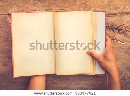 hands holding the old open book on old wooden table - stock photo