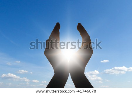 hands holding the sun - stock photo