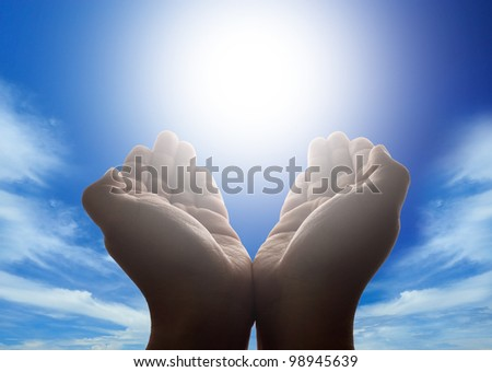 Hands holding the sun with cloudy blue sky in background - stock photo