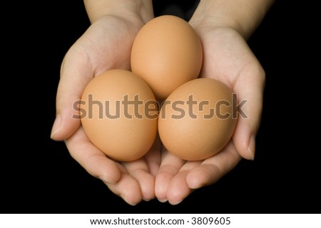 Hands holding three eggs isolated on black background - stock photo