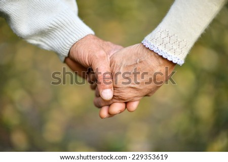 Hands holding together on a natural background - stock photo