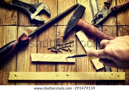 Hands holding tool. Hammer, flat file, pliers, screwdriver, monkey wrench, screws, board and blade on natural wooden background. - stock photo