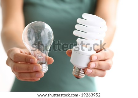 Hands holding traditional and energy efficient light bulbs - stock photo