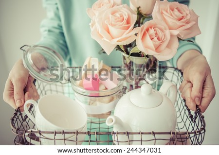 Hands holding tray with roses, white teapot, cups and valentine's paper hearts in retro jar. Toned picture - stock photo
